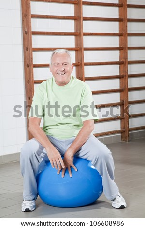 Happy Senior man sits on a fitball.