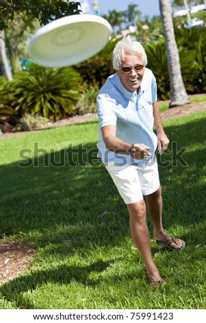 Happy senior man throwing a frisbee outside in a park in sunshine - stock photo