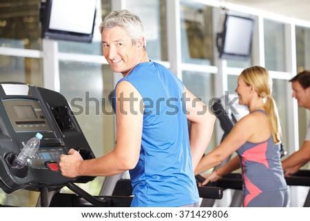 Happy senior man training in a fitness center on the treadmill - stock photo