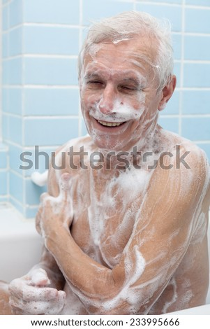 Happy senior man washing his body with soap in bath. - stock photo