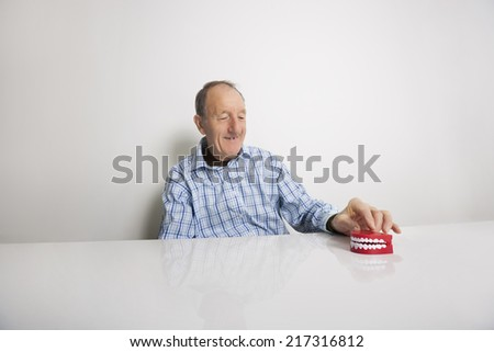 Happy senior man with dentures at table - stock photo