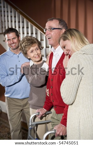 Happy senior man with walker at home with family - stock photo