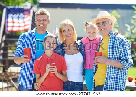 Happy senior man, young couple and their two children looking at camera  - stock photo