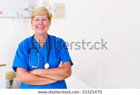 Happy senior nurse standing with hands folded in hospital ward - stock photo
