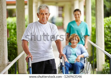 Happy senior people in nursing home with walker and wheelchair - stock photo