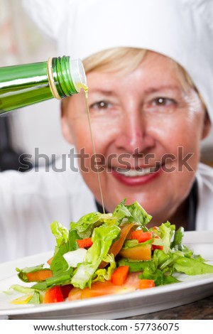 happy senior professional chef pouring olive oil on salad - stock photo