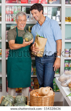 Happy senior salesman assisting male customer in buying vegetables at supermarket - stock photo
