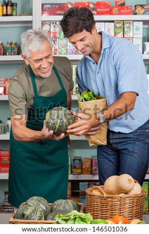 Happy senior salesman assisting male customer in shopping vegetables at supermarket - stock photo