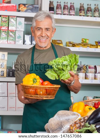 Happy senior salesman selling vegetables in grocery store - stock photo