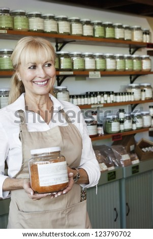 Happy senior salesperson with jar looking away in spice store - stock photo