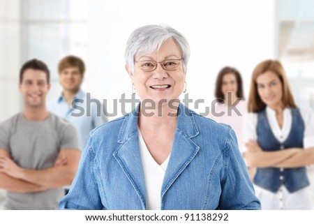 Happy senior teacher looking at camera smiling students in background.?