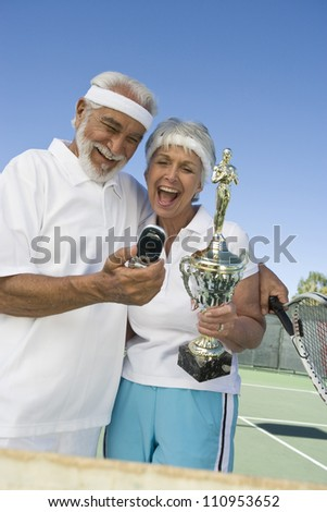 Happy senior tennis player after winning - stock photo