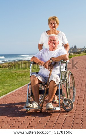 happy senior wife push husband on wheelchair at beach - stock photo