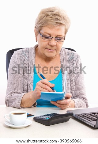 Happy senior woman, an elderly pensioner writing notes or calculation in notebook or calendar - stock photo