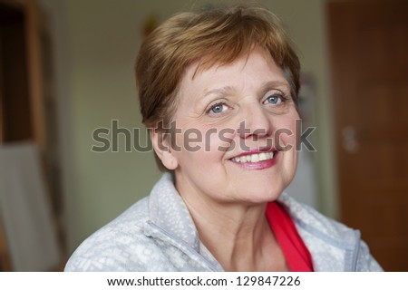 happy senior woman at home - bokeh background - stock photo