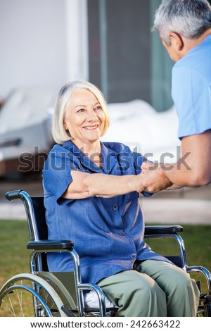 Happy senior woman being assisted by male nurse to get up from wheelchair at nursing home yard - stock photo