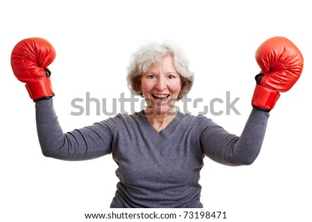 Happy senior woman cheering with red boxing gloves