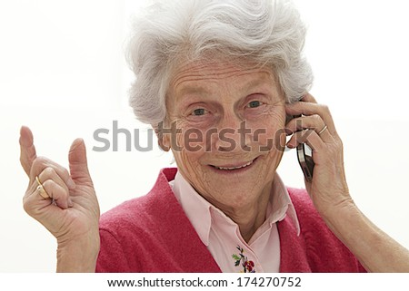 Happy senior woman conversing on the phone - stock photo