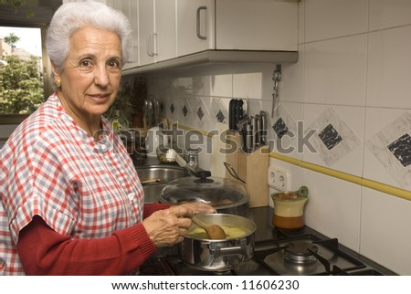 Happy senior woman cooking at home - stock photo