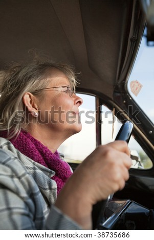 Happy senior woman driving an oldtimer car - stock photo