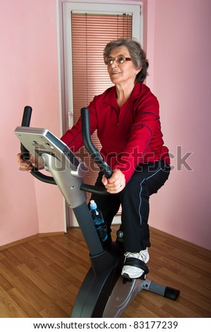 happy senior woman exercise on spinning bicycle at home - stock photo