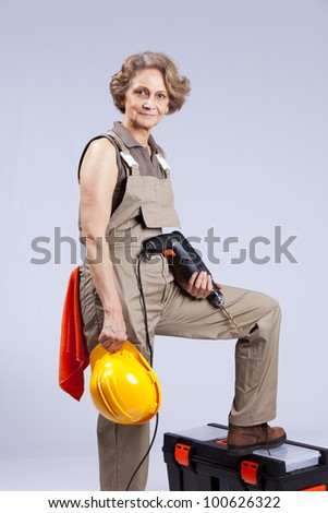 Happy senior woman holding a drill tool (isolated on gray) - stock photo