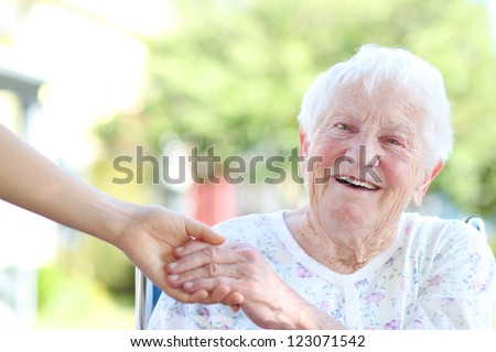 Happy senior woman holding hands with caretaker - stock photo