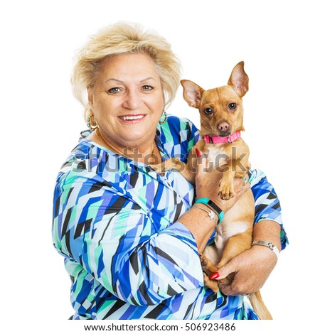Happy senior woman holding little Chihuahua dog. Both looking into camera.