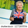 Happy Senior Woman Holding United Kingdom Flag, Indoors - stock photo