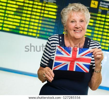 Happy Senior Woman Holding United Kingdom Flag, Indoors - stock photo