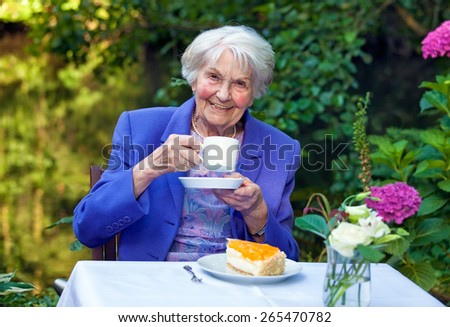Happy Senior Woman in Trendy Business Suit, Sitting at the Garden Table with a Slice of Cake, Holding a Cup of Coffee While Looking at the Camera. - stock photo