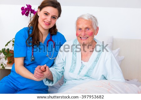 Happy senior woman laying in bed in a well equipped luxury nursing home with a caring nurse supervising her 24/7.