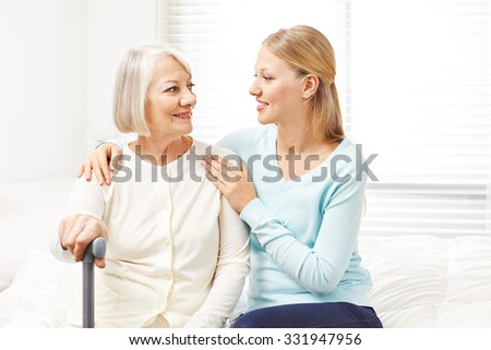 Happy senior woman looking at her granddaughter at home - stock photo