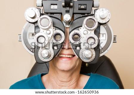 Happy senior woman looking through phoropter during eye exam - stock photo