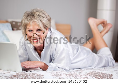 Happy senior woman lying on bed and browsing through laptop - stock photo