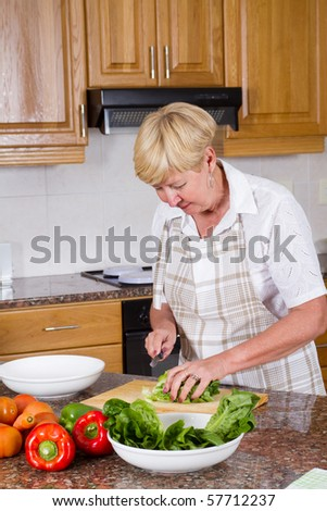 Happy senior woman making a healthy salad in kitchen - stock photo