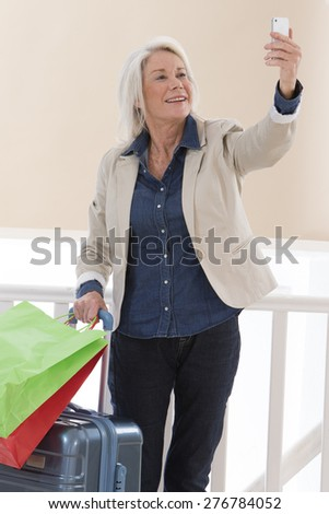 happy  senior woman picturing herself with  smart phone smiling while holding her luggages and shopping bags - stock photo