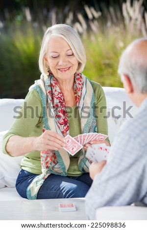 Happy senior woman playing cards with man at nursing home porch - stock photo