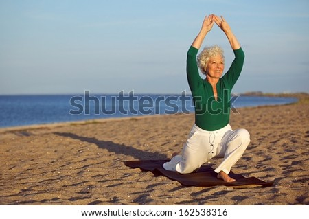 Happy senior woman practicing yoga on the sandy beach. Mature caucasian woman stretching legs and arms on the seashore. Healthy lifestyle and fitness concept - stock photo