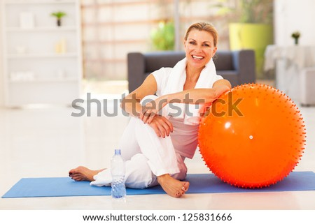 happy senior woman resting on mat after exercise at home - stock photo