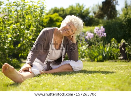 Happy senior woman sitting down on grass comfortabley in garden looking at you - Outdoors - stock photo