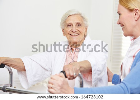 Happy senior woman sitting with geriatric nurse on her bed - stock photo