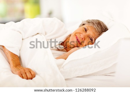 happy senior woman sleeping on bed - stock photo