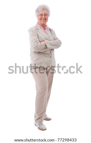 Happy senior woman standing  with her arms crossed - stock photo
