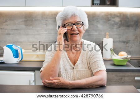 Happy senior woman talking on smartphone at home. - stock photo