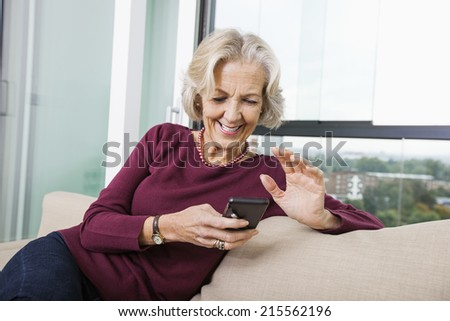 Happy senior woman text messaging through smart phone on sofa at home - stock photo