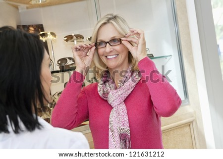 Happy senior woman trying on glasses in store - stock photo