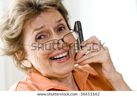 Happy senior woman using mobile phone - stock photo