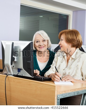 Happy Senior Woman With Classmate Using Computer In Class - stock photo