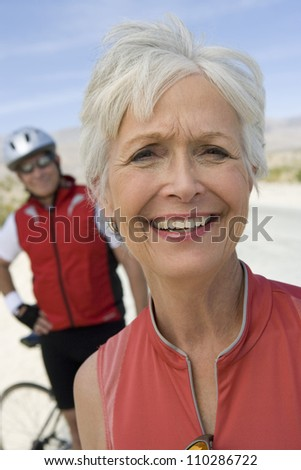 Happy senior woman with man in the background